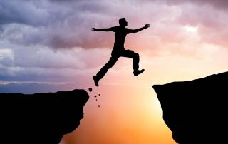 man jumping between peaks
